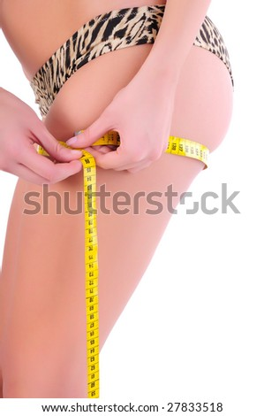 Closeup of young woman in the underwear measuring her thigh size