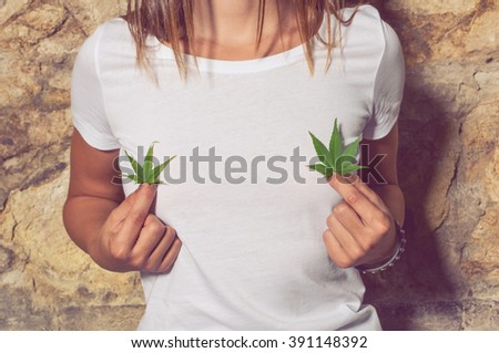 Closeup of young woman sitting outside and holding cannabis green leaves in her hands - stock photo