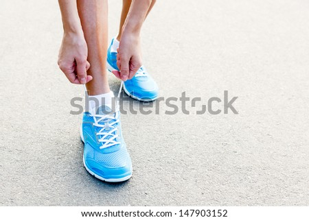 Closeup of Young Woman Tying Sports Shoe - concept image - stock photo