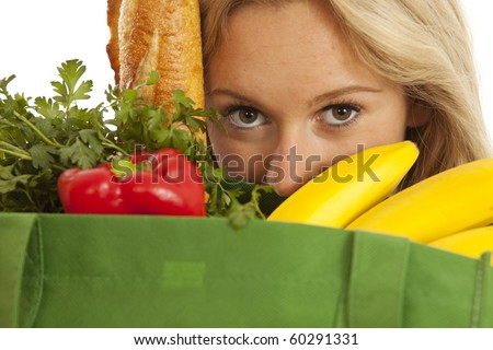 Closeup of young woman with green recycled grocery bag of healthy food and vegetables - stock photo
