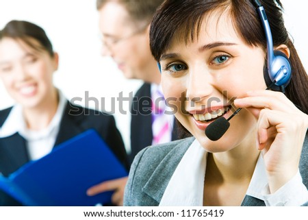 Closeup of young woman with headset looking at camera with smile in working environment - stock photo