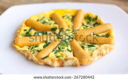 Closeup omelette with sausages and herbs on white plate - stock photo