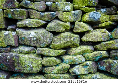 Closeup on a dry stone wall in yorkshire countryside, UK. Building materials pattern - stock photo