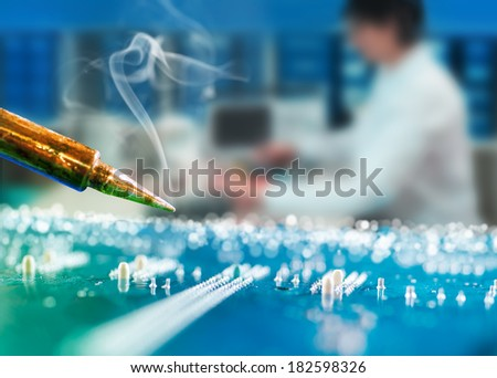 Closeup on a hot soldering iron in service centre, shallow DOW, technical background - stock photo