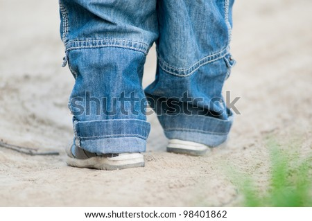 Closeup on a kids feet wearing grey sandals and jeans over ground - stock photo
