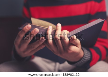 Closeup on a man reading a big heavy book - stock photo