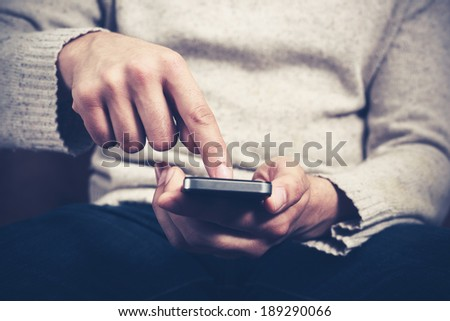 Closeup on a man's hands as he is sitting on a sofa and using a smartphone - stock photo