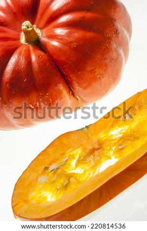 Closeup on a slice of orange pumpkin with pulp and seeds in the foreground.  - stock photo
