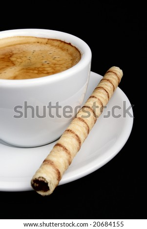 Closeup on a white cup of coffee (espresso) with a rolled wafer. - stock photo