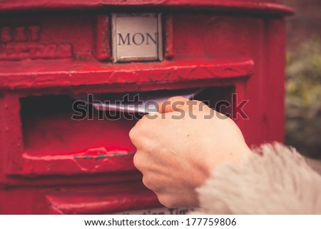 Closeup on a woman's hand as she is posting a letter - stock photo