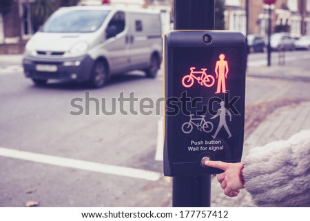 Closeup on a woman's hand as she is pushing a button at pedestrian crossing - stock photo
