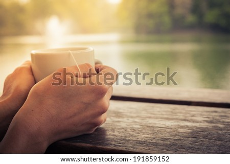 Closeup on a woman's hands holding a cup of tea by a lake in the afternoon - stock photo