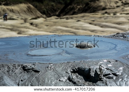 Closeup on an active muddy volcano cone with mud bubbles coming out - stock photo