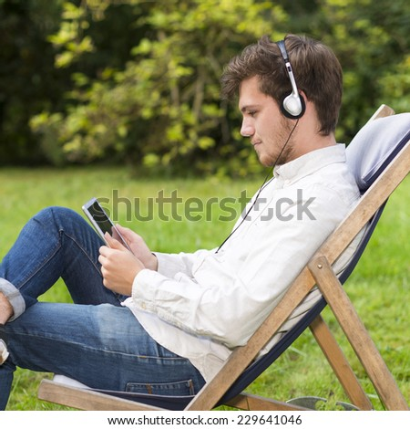 Closeup on an attractive bearded young student listening to music with headphones sitting on profile in the garden. He is holding and looking his digital tablet at the same time. - stock photo