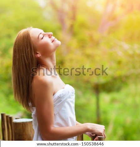 Closeup on beautiful calm woman enjoying nature on terrace in luxury cottage, spa resort, zen balance, summer vacation, harmony conception