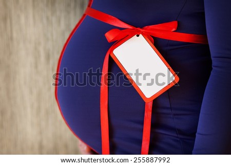 Closeup on belly of expectant woman with red ribbon and label - stock photo