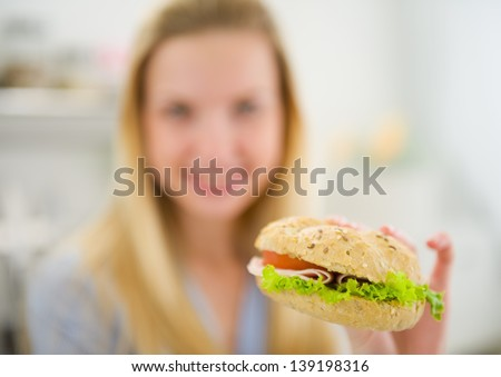 Closeup on burger in hand of teenager girl