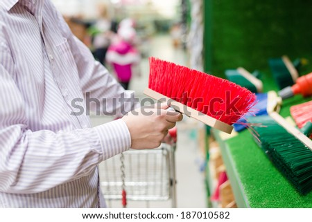 closeup on business man selecting or choosing and buying a sweeping broom for floor or path on the DIY department shopping store background - stock photo