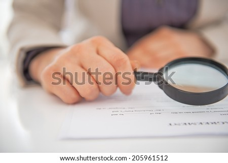 Closeup on business woman exploring document with magnifying lens - stock photo