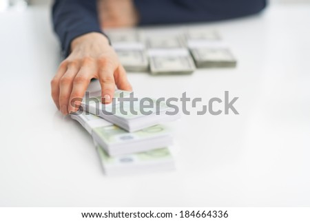 Closeup on business woman giving money packs