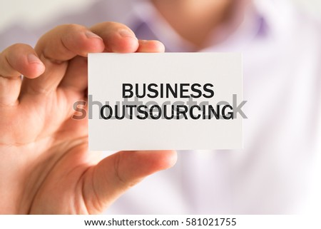 Closeup on businessman holding a card with text BUSINESS OUTSOURCING, business concept image with soft focus background