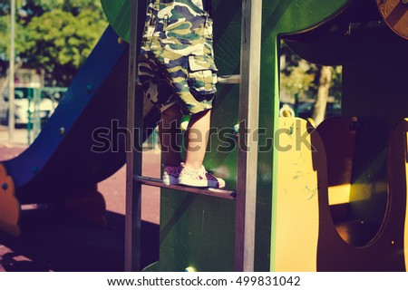 Closeup on child legs active in the playground on city park outdoors background