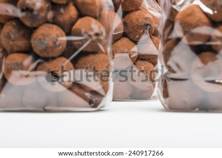 Closeup on Christmas chocolate truffles stacked in plastic bags. Copy space. Shooting on white background in studio. - stock photo