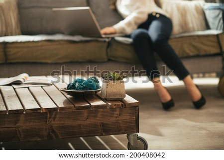 Closeup on coffee table and young woman using laptop in background - stock photo