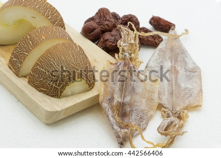 Closeup on cooking ingredients for making traditional Chinese healthy soup for removes body heat and replenishes calcium. Fresh old cucumber slices, dried cuttlefish and red dates on white background.