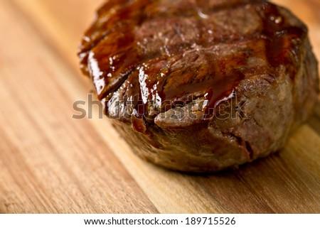 closeup on delicious steak on wooden kitchen board - stock photo
