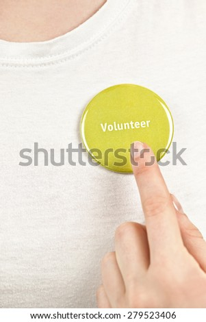 Closeup on female hand pointing to green volunteer button - stock photo