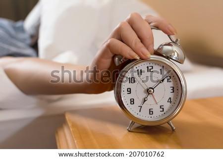 Closeup on female hand reaching to turn off alarm clock. - stock photo