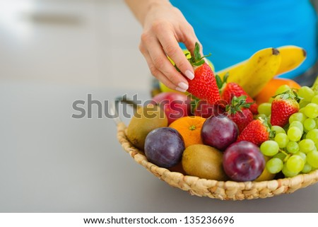 Closeup on female hand taking strawberry from plate of fresh fruits - stock photo