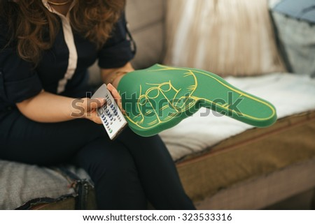 Closeup on football fan woman sitting on sofa in loft living room and watching tv. Modern lifestyle concept. - stock photo