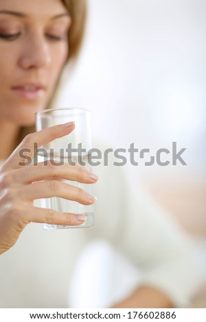 Closeup on glass of water held by woman's hand - stock photo