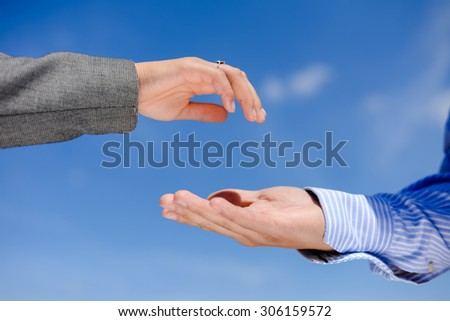 Closeup on hand giving and hand receiving on blue sky outdoors background, copys space picture