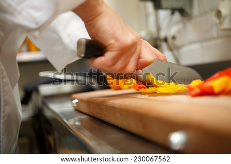 closeup on hands cutting yellow pepper on professional kitchen - stock photo