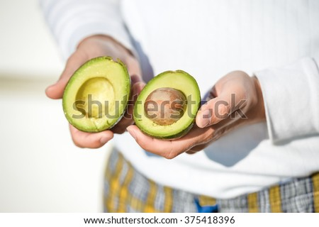 Closeup on hands holding fresh avocado cut in half on light background - stock photo