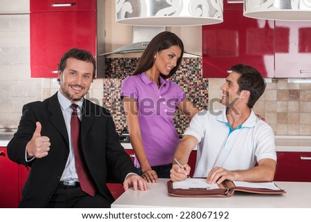 closeup on happy man signing agreement on new house. thumb up to young couple purchasing new kitchen and looking at each other - stock photo