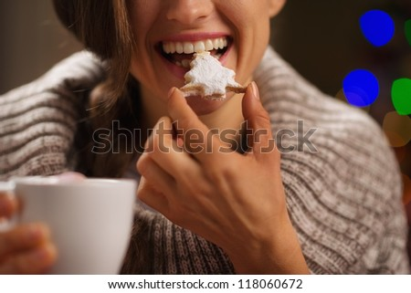 Closeup on happy woman eating Christmas cookie in front of Christmas lights - stock photo