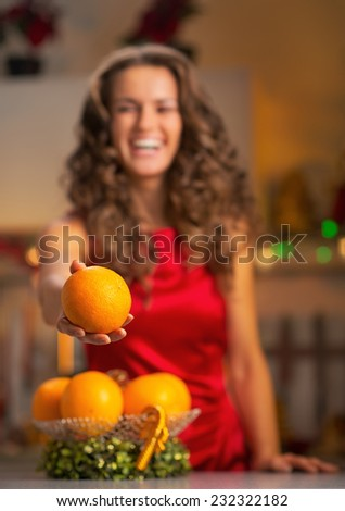Closeup on happy young housewife giving orange - stock photo