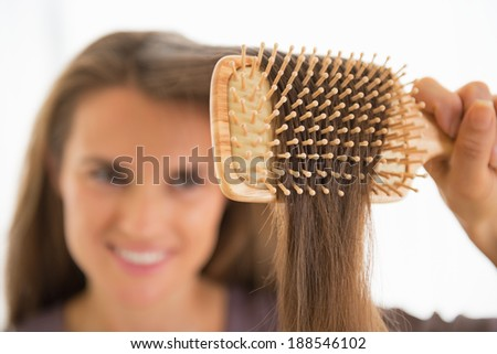 Closeup on happy young woman combing hair