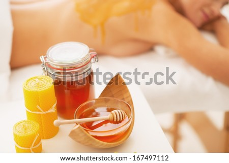 Closeup on honey spa therapy ingredients and relaxed young woman in background