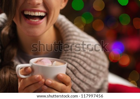 Closeup on hot chocolate with marshmallows in hand of happy woman