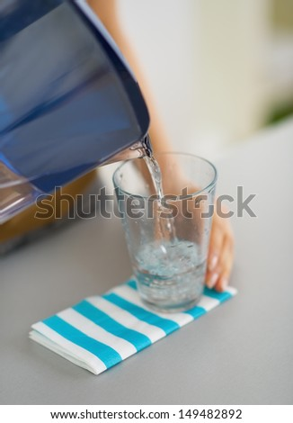 Closeup on housewife pouring water into glass from water filter pitcher - stock photo