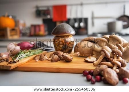 Closeup on jar of pickled mushroom on cutting board - stock photo