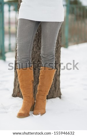Closeup on legs of woman leaning against tree in winter park