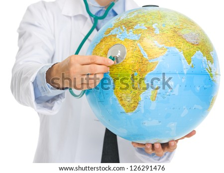 Closeup on medical doctor woman listening globe with stethoscope - stock photo