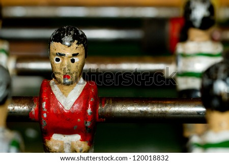 Closeup on miniature metallic ball players of a Foosball table soccer game - stock photo