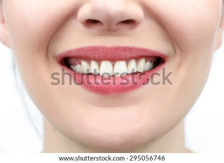 Closeup on mouth of females smiling face - stock photo